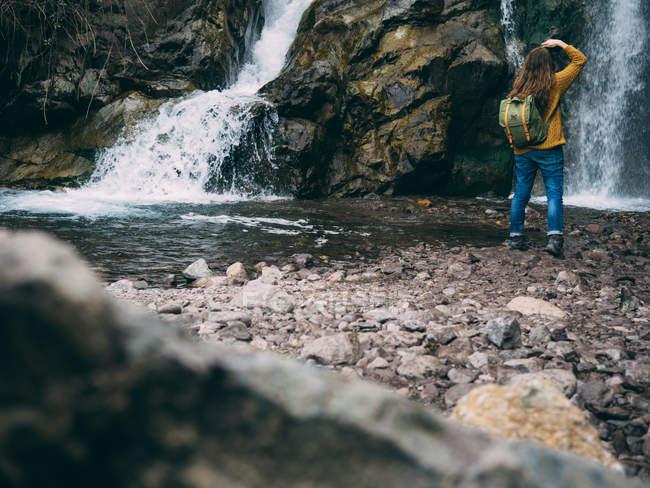 Donna con lo zaino esplorare cascata — Foto stock