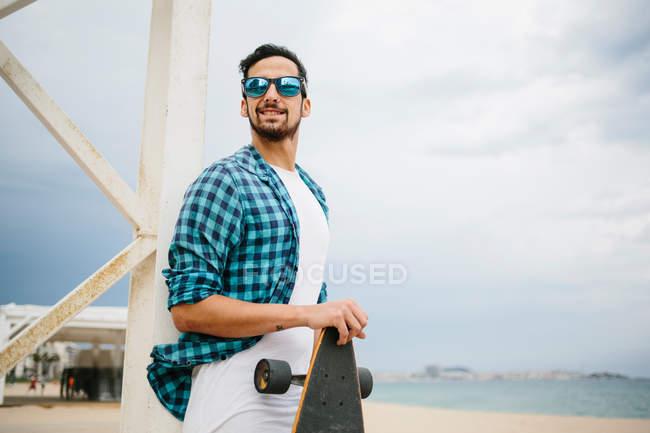 Homem com skate na praia — Fotografia de Stock