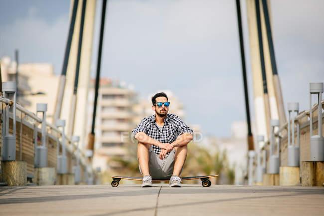 Homme assis sur skateboard sur route vide — Photo de stock