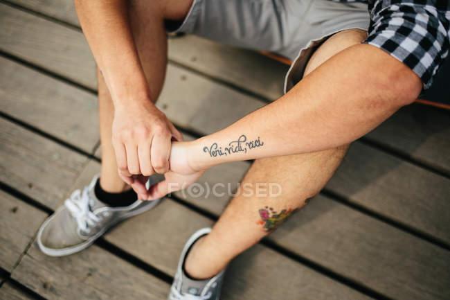 Homme avec des tatouages assis sur le sol en bois — Photo de stock