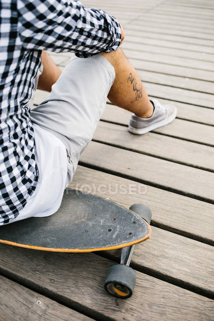 Tattooed man sitting on skateboard — Stock Photo