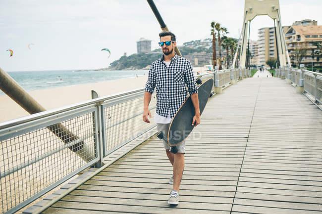 Hombre caminando en el muelle con monopatín - foto de stock