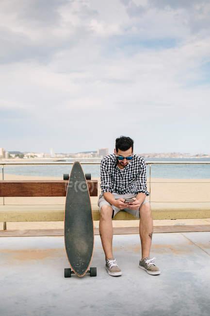 Uomo vicino skateboard e utilizzando il suo smartphone . — Foto stock