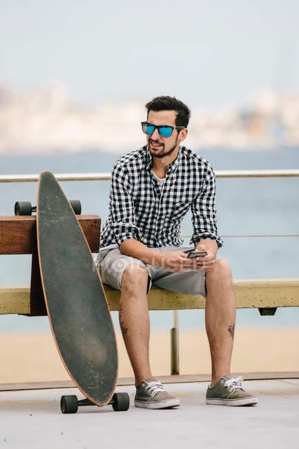 Junger Mann sitzt auf der Bank mit smartphone — Stockfoto