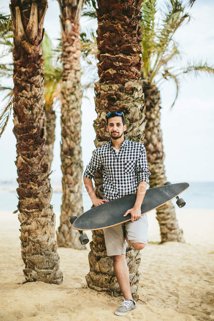 Man in summer apparel with longboard — Stock Photo