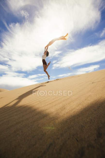 Женщина в момент прыжка в пустыне — стоковое фото