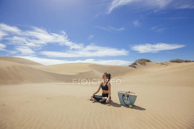 Woman practicing yoga in desert — Stock Photo