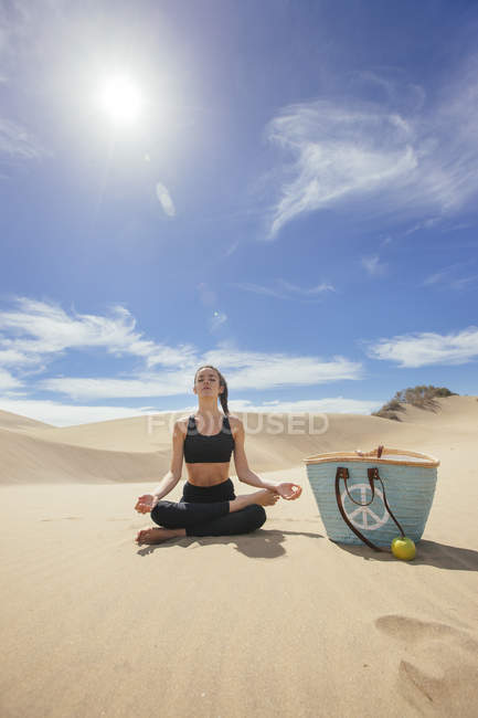 Woman practicing yoga in desert — Stock Photo