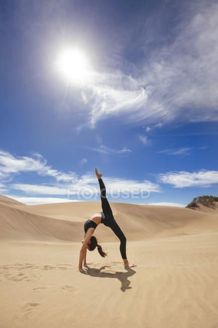 Женщина растягивает тело в пустыне — стоковое фото