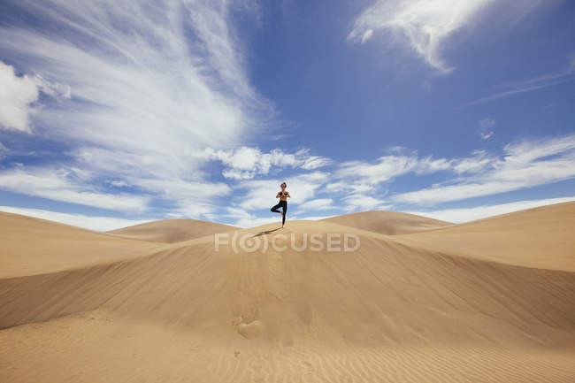 Frau praktiziert Yoga im Sand — Stockfoto