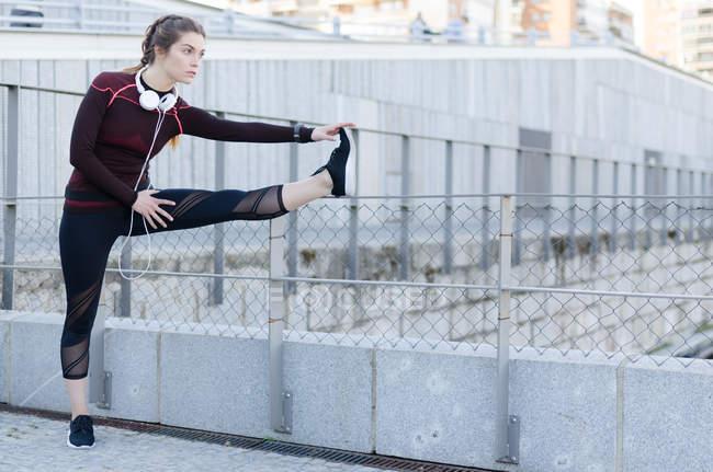 Женщина растягивается после бега — стоковое фото