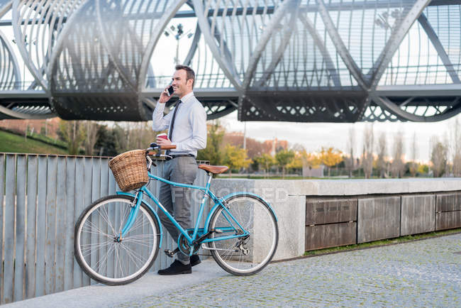 Business man standing by bicycle — Stock Photo