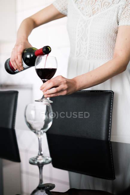 Жінка розливу червоне вино — стокове фото