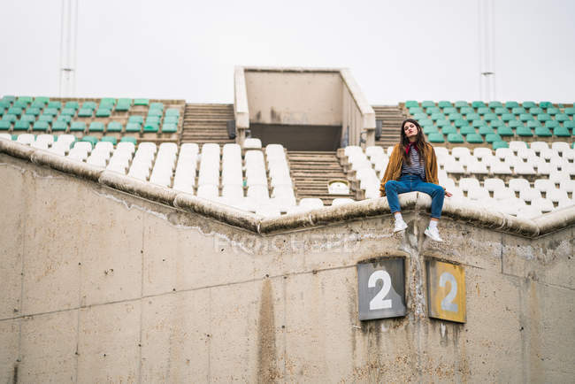 Young cute girl in abandoned stadium — Stock Photo