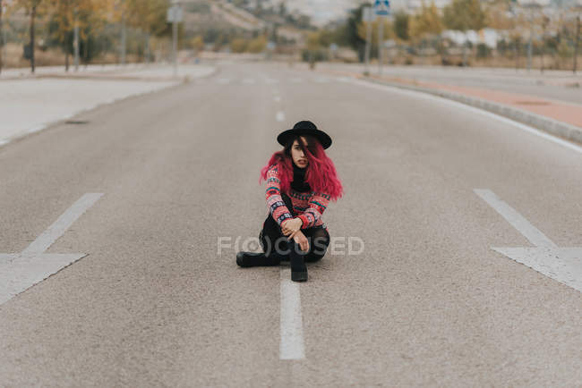 Girl with pink hair in hat sitting on roadway — Stock Photo