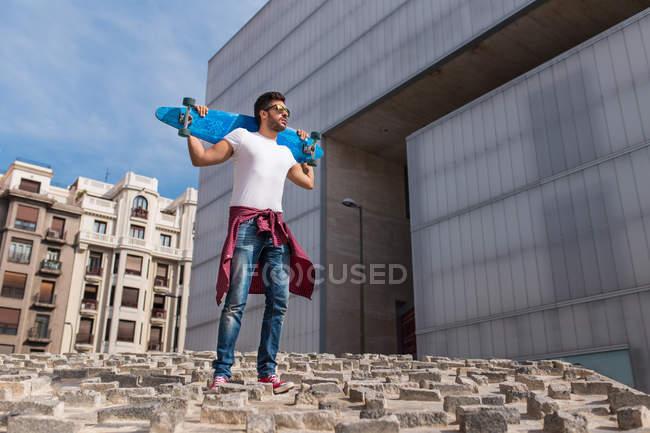 Stylish skateboarder on street — Stock Photo