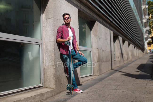 Trendy man posing with longboard on street — Stock Photo