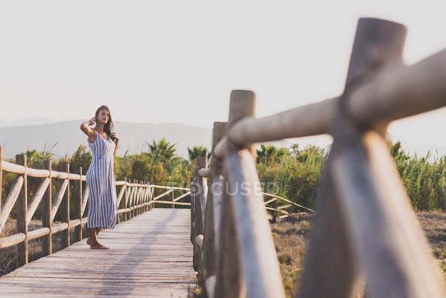 Женщина в платье на деревянной дорожке — стоковое фото