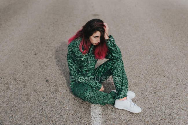 Depresssed girl sitting on road — Stock Photo