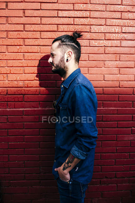 Stylish hipster against brick wall — Stock Photo