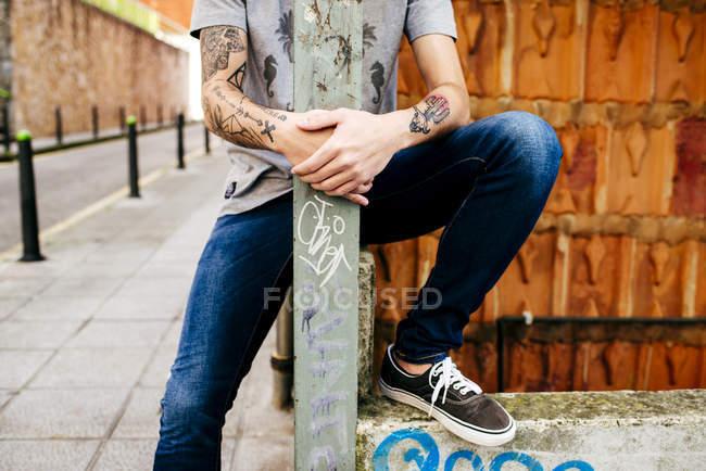 Homem posando atrás de poste de metal — Fotografia de Stock