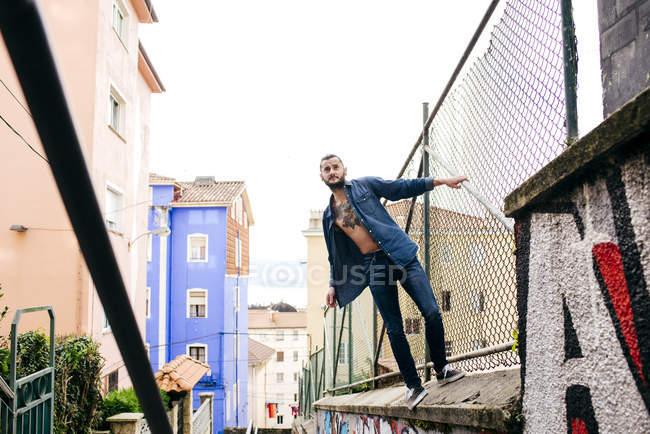 Man in denim posing on metal fence — Stock Photo