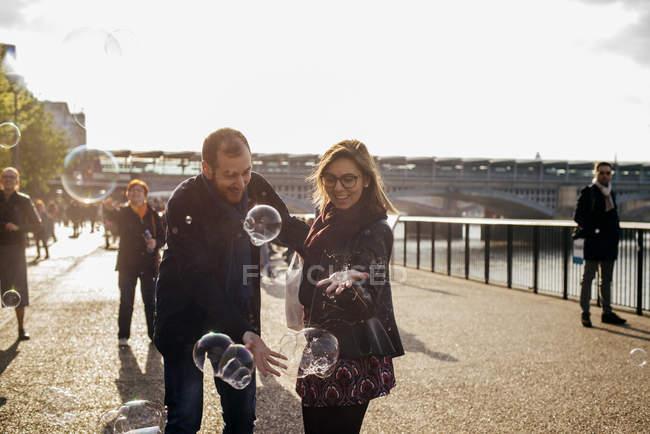 Счастливая пара веселится с пузырьками — стоковое фото