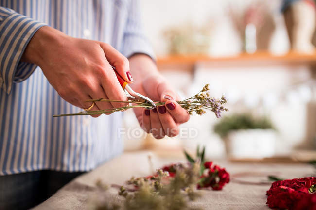 Anonymous woman cropping flowers in workshop — Stock Photo