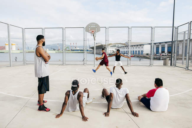 Men watching others playing basketball — Stock Photo