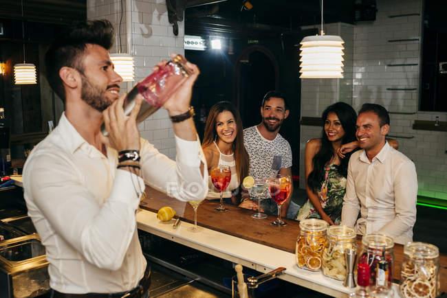 Menschen beobachten Barkeeper in der Bar — Stockfoto