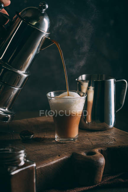 Pouring hot coffee into glass — Stock Photo