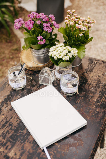 Notebook on table with flowers — Stock Photo