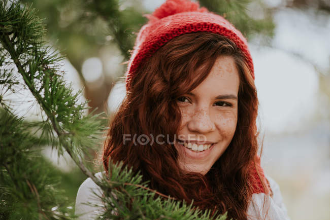 portrait of a smiling freckled girl in red knitted hat among fir