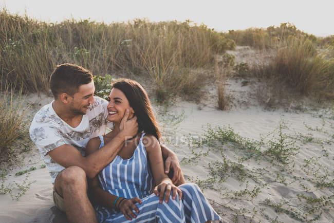 Coppia allegra seduta sulla spiaggia — Foto stock