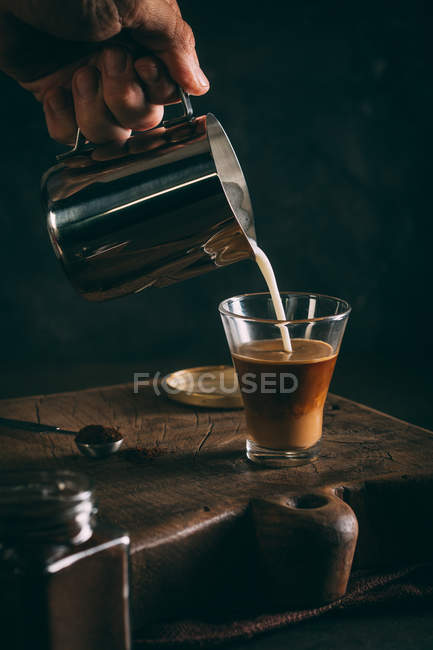 Pouring hot milk into glass — Stock Photo