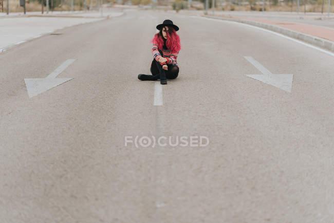 Дівчинка сидить на проїжджу частину з схрещеними ногами — стокове фото