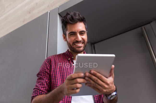 Hombre alegre con la tableta - foto de stock
