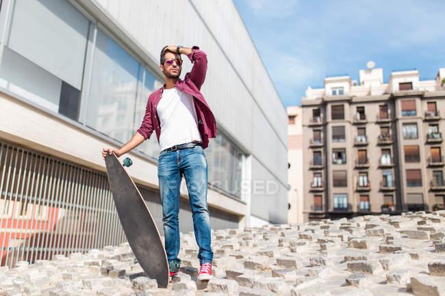 Homme élégant posant avec longboard — Photo de stock