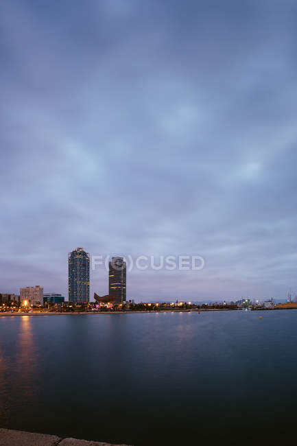 Landscape of coastline with skyscrapers against dusk sky — Stock Photo