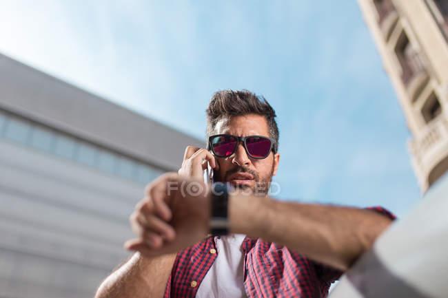 Homem falando telefone e olhando para assistir — Fotografia de Stock