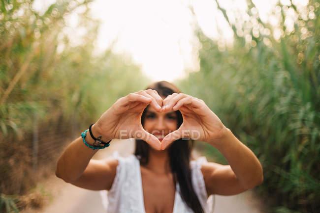 Женщина делает форму сердца руками — стоковое фото