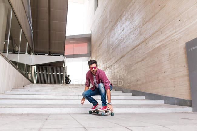 Trendy man riding skateboard — Stock Photo