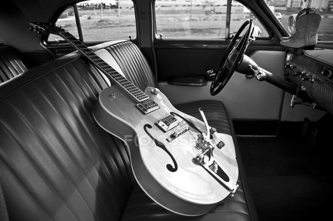 Vintage guitar on a car seat — Stock Photo