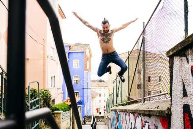 Homem sem camisa em movimento sobre fundo urbano — Fotografia de Stock