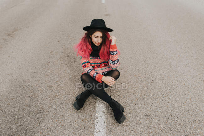 Girl in hat sitting on roadway — Stock Photo