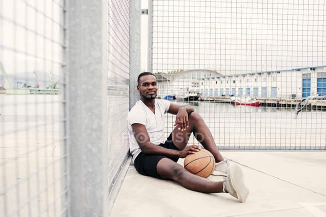 Уверенный человек, сидящий с баскетболом — стоковое фото