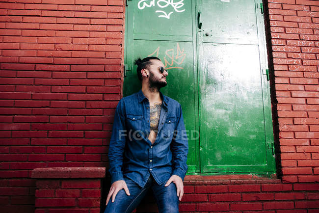 Bearded hipster leaning on brick wall — Stock Photo
