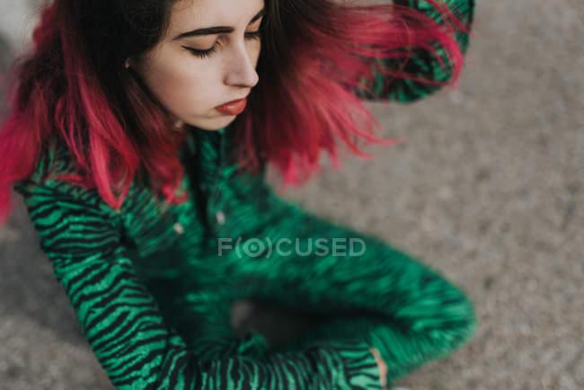 Girl with pink hairsitting on asphalt — Stock Photo