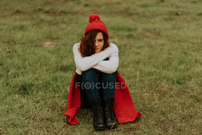 A girl in a red hat sits in a meadow — Stock Photo