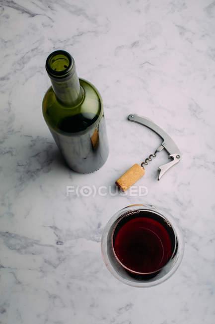Vinho tinto e vidro na mesa de mármore — Fotografia de Stock